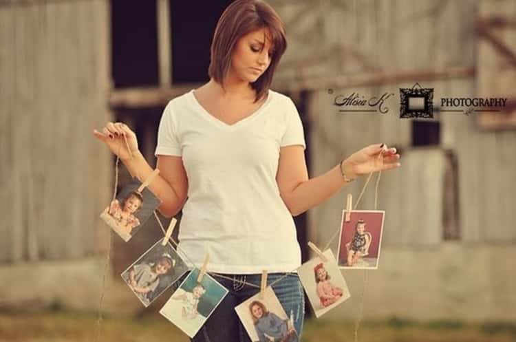 senior picture ideas for girls - woman holding up a garland of growth progression photos