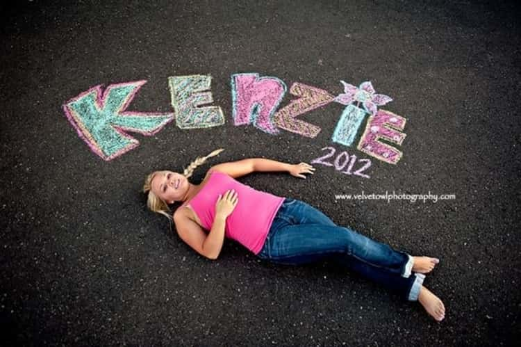 Senior picture ideas for girls - girl lying on sidewalk with her name and graduation year inscribed on sidewalk