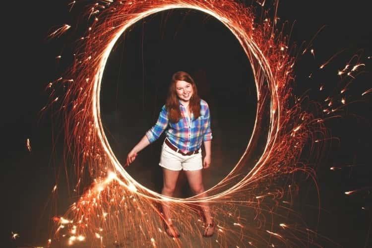 girl holding lit sparkler in the dark