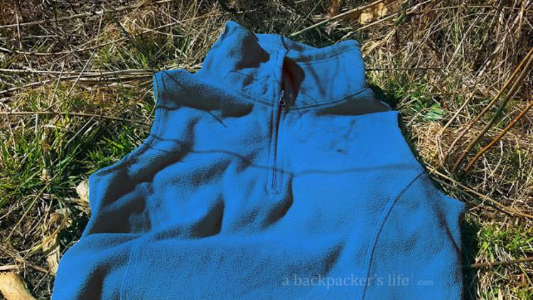cold-weather-camping image of a fleece vest on the grass