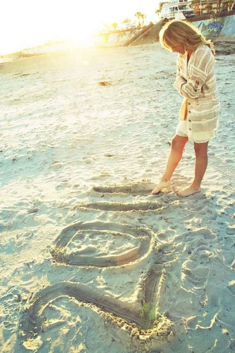 senior picture ideas for girls - girl on beach writing in the sand with her toes