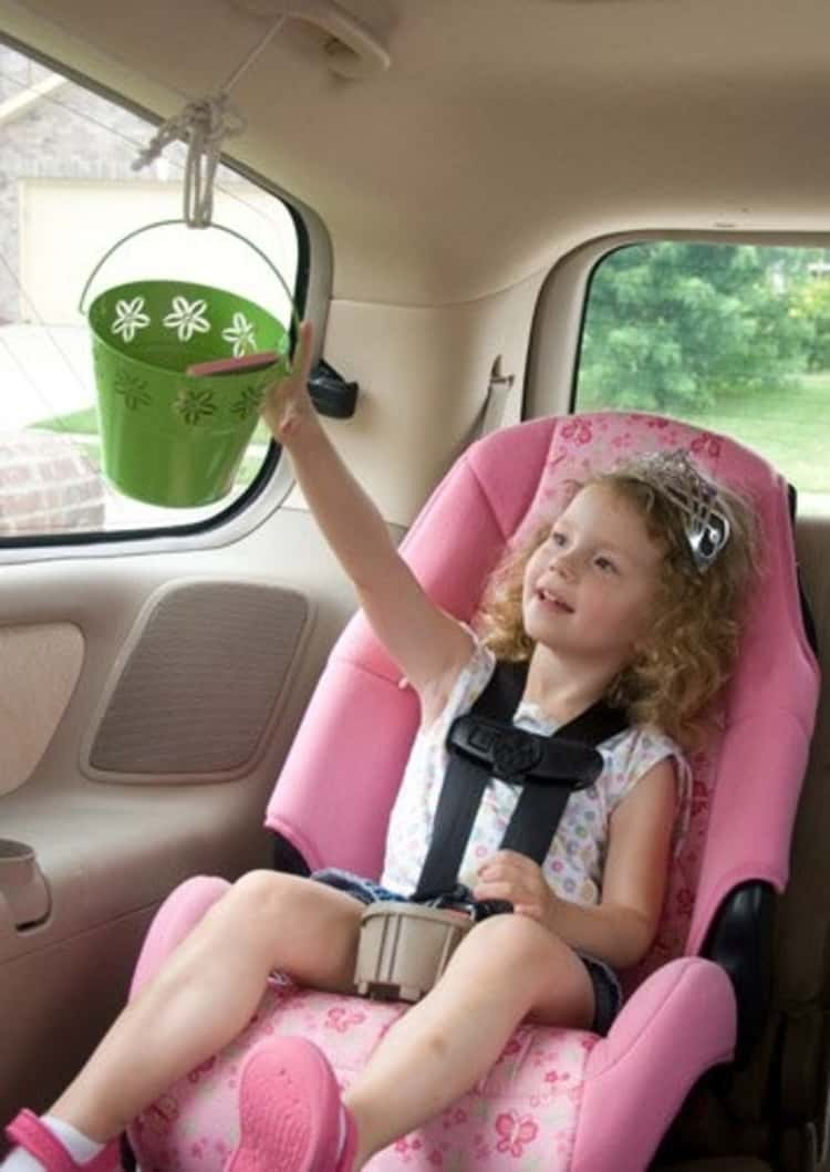 Travel hack little girl in car seat using a pulley system to move a bucket from front to back of car easily