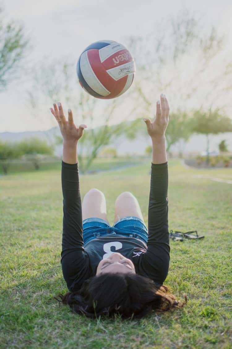 senior picture ideas for girls - girl lying down on her back and while throwing up a volleyball