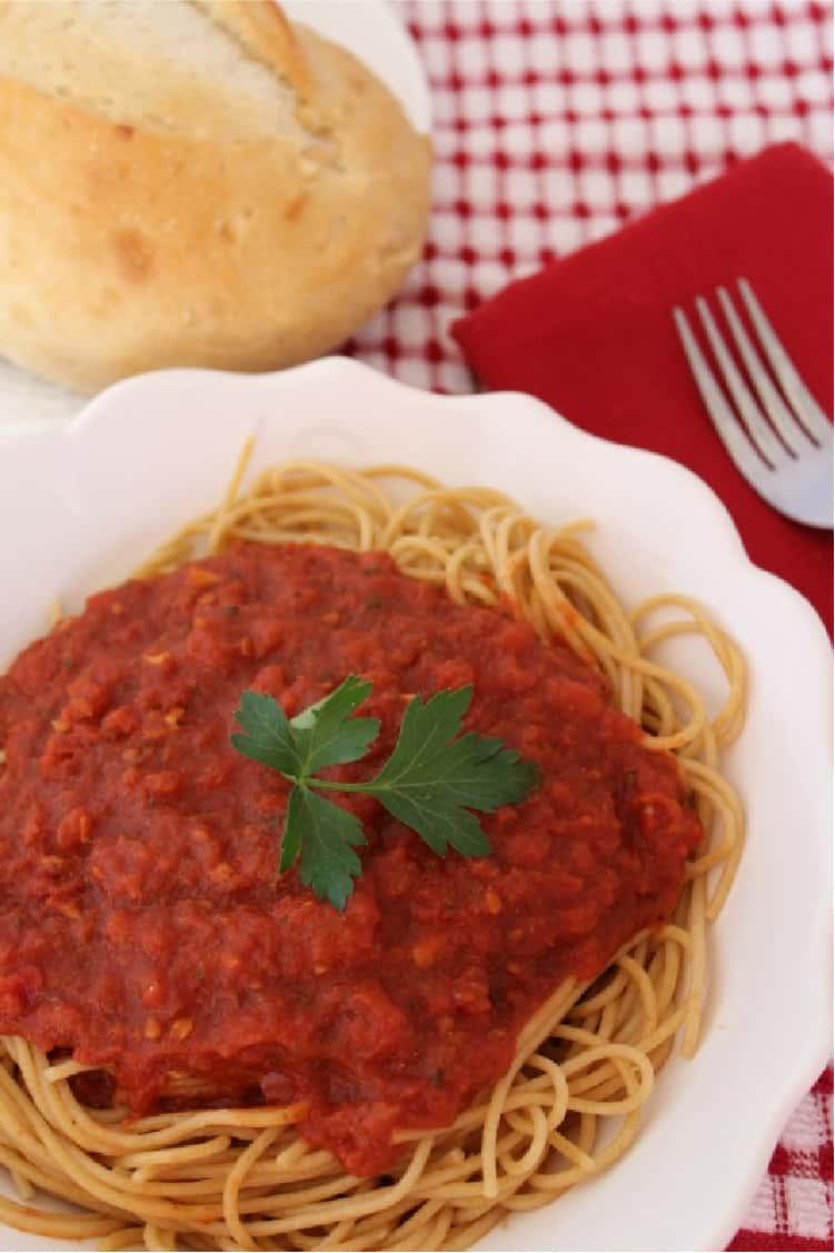 Marinara Sauce over a spaghetti pasta dish in a white plate
