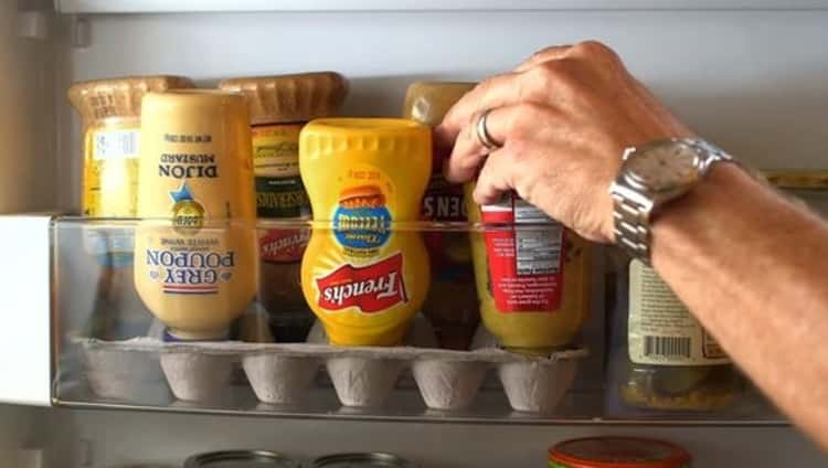 organize your fridge by using an egg carton to store your condiment bottles upside down