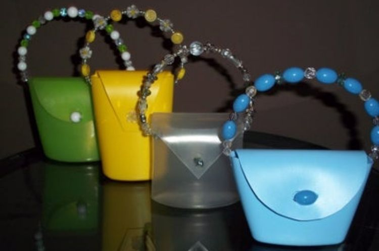 Kids craft play purses from folded soap bottles, wires, and beads.