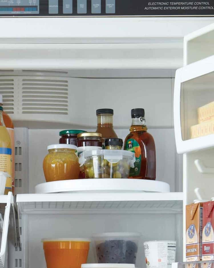 Organize your fridge space by placing condiments on a lazy susan