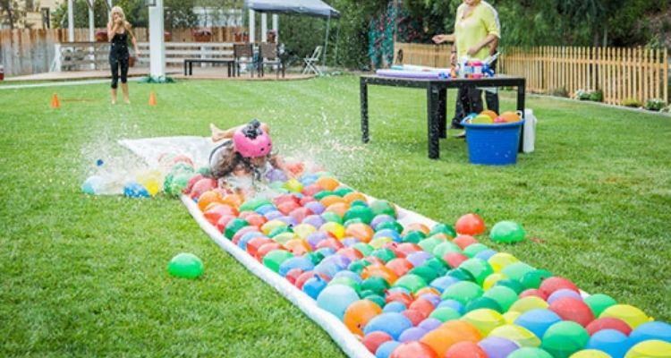 Child sliding on a water balloon slip and slide