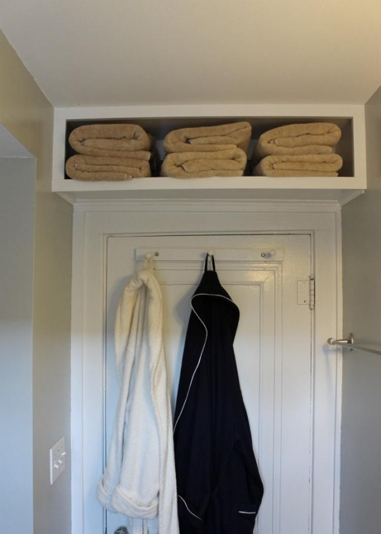 Shelf above door to create extra storage space in small rooms. Hooks on back of door to hold robes.