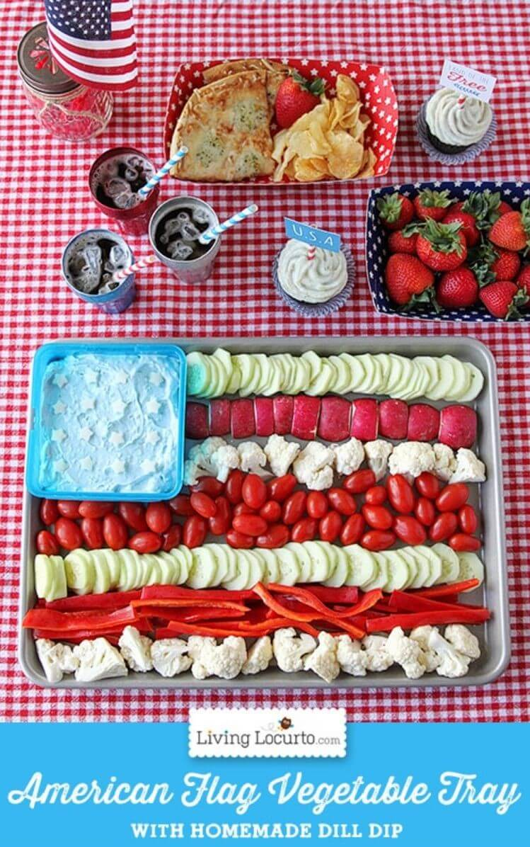 A table with a veggie tray shaped like an American flag, drinks, strawberries, and veggie dip for a 4th of July BBQ