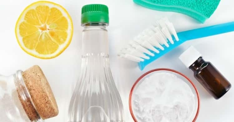 cleaning wood cabinets - assorted cleaning items such as brush, rag, piece of lemon, bottle of essential oil and bottle of a clear liquid.