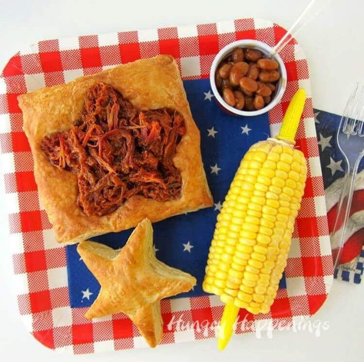A puff pastry filled with bbq with corn on the cob and baked beans on the side