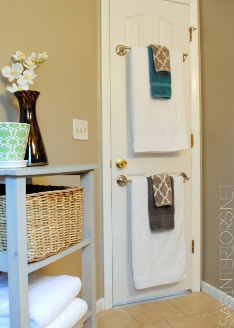 Towel Rods hanging on the back of door holding cute towel sets. The main towel is white and the accent towels are blue and brown.
