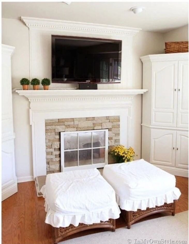 Cable management in a living room by wrapping tv cords in fabric that matches the cream colored wall paint