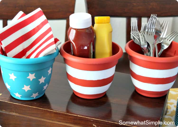 Flower pots painted and decorated differently used as a condiment and utensil station for a 4th of July themed party