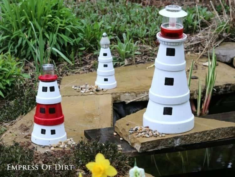 Three DIY flower pot lighthouses placed in a garden