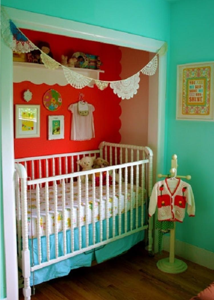 Repurpose a closet into a nursery space or office. This one features a white crib with a red wall and white accent shelves.