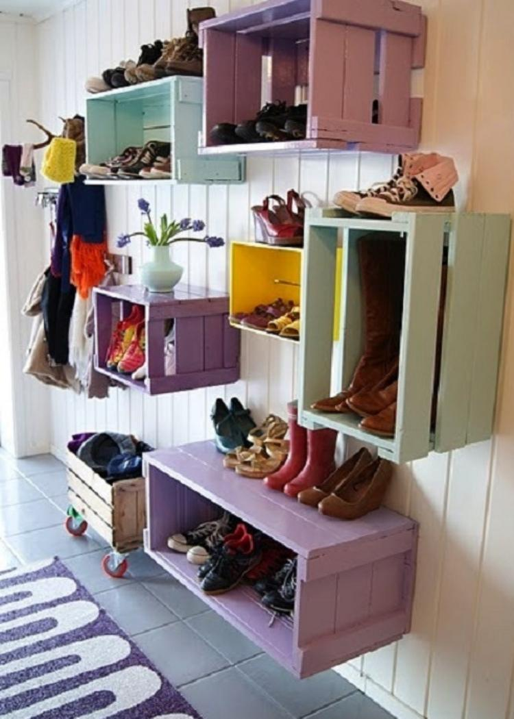Colorful crates attached to wall hold shoes and other belongings. Great idea for organizing small mud room.