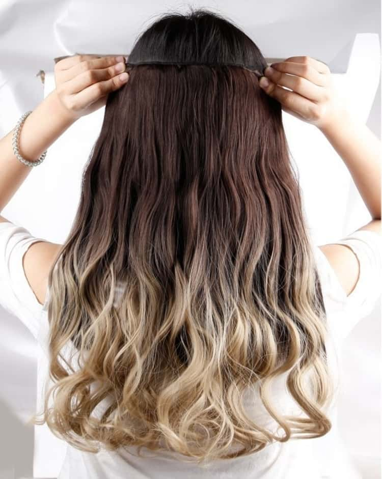 a photo showing a lady adding hair extensions to give more volume to her hait