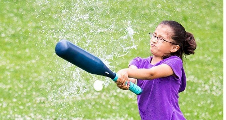 Girl hitting water balloon with baseball bat