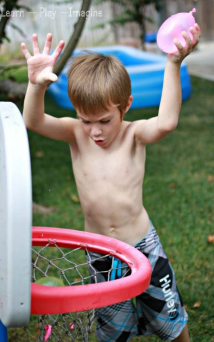 Boy playing Basketball with water balloons