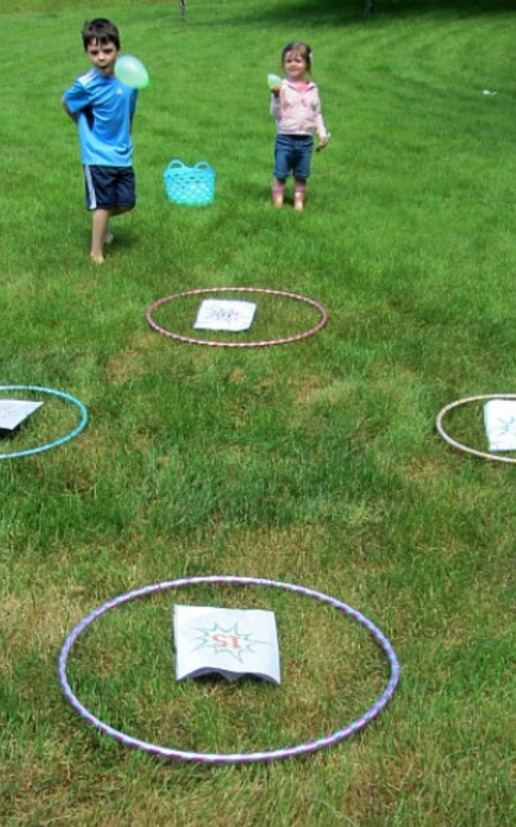 Kids throwing water balloons into hula hoops while doing math