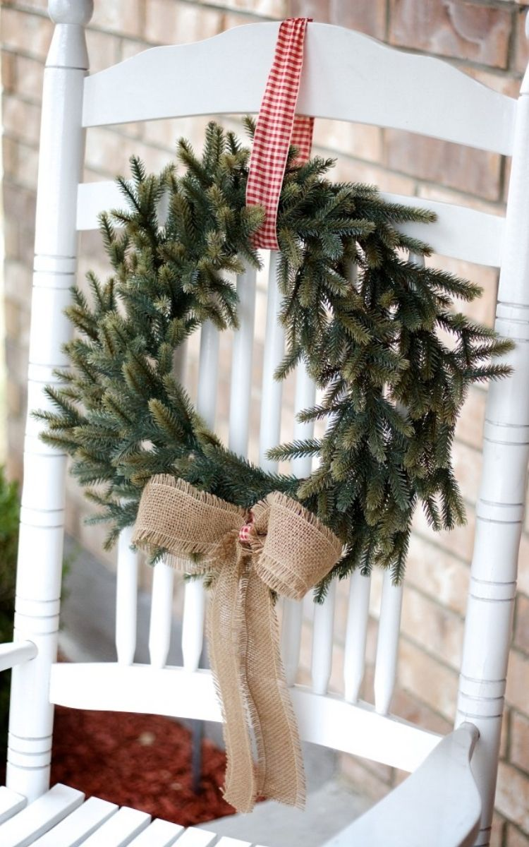 Fresh wreath tied to a wooden white chair