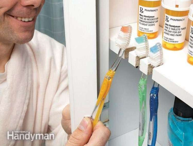 OneCrazyHouse DIY Home Organization open medicine cabinet with a man smiling and reaching for a toothbrush that is stored in small opening on the medicine cabinet shelf