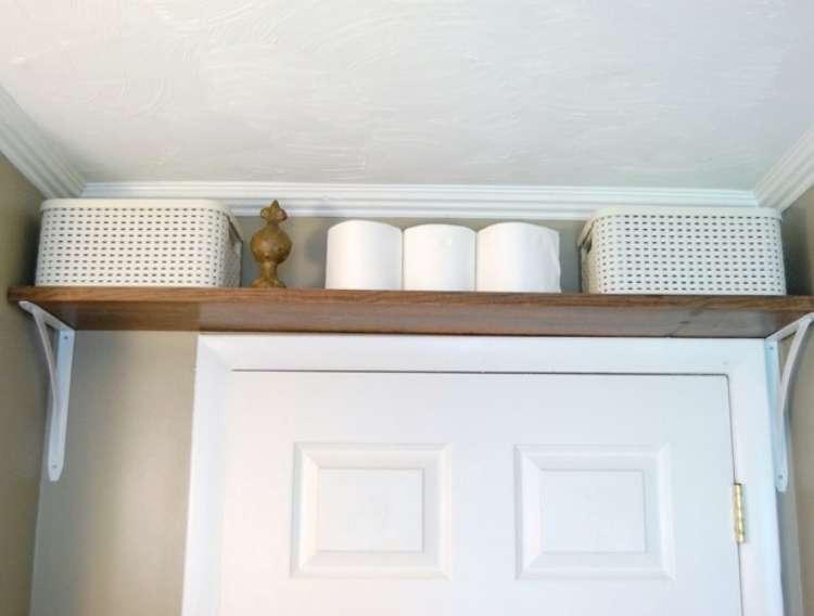OneCrazyHouse DIY Home Organization shelf installed right above bathroom doorframe for storage