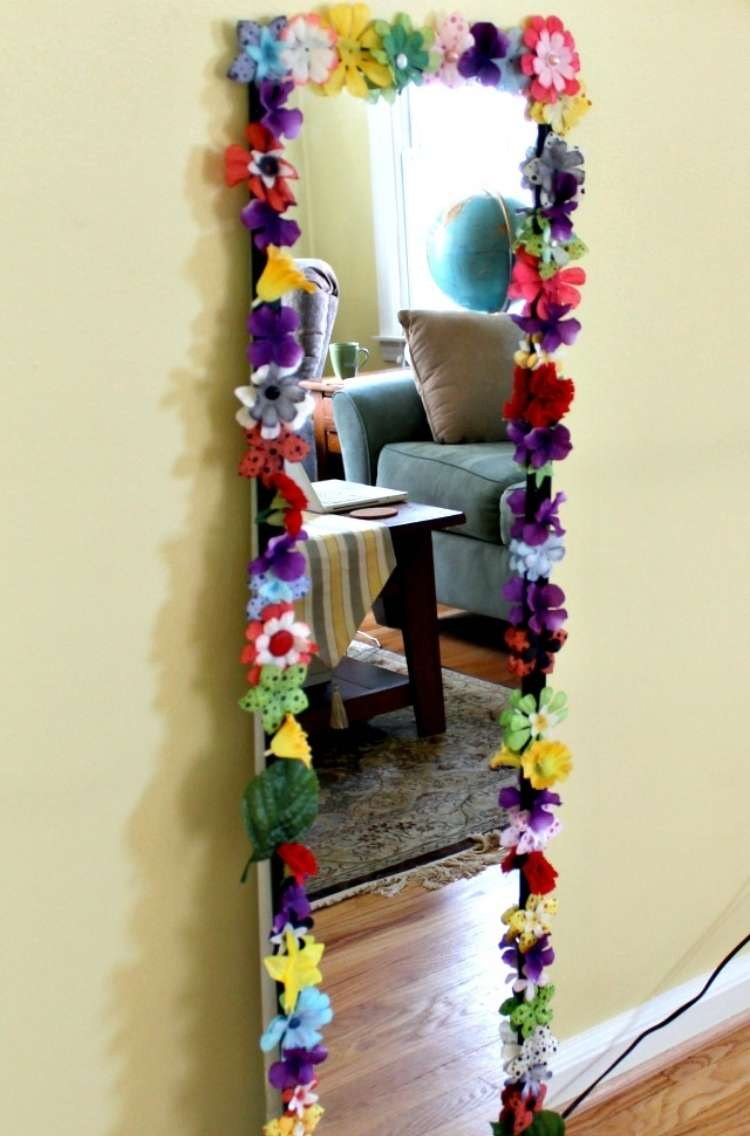 OneCrazyHouse Dorm Room Decor mirror leaning against wall with plastic flowers glued to the rim of the mirror