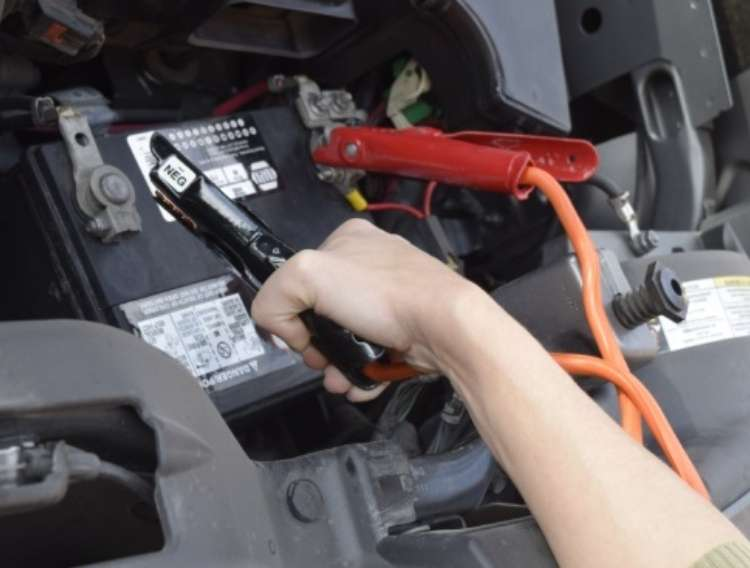 OneCrazyHouse Easy Car Repairs hand holding one of the clips for the jumpstarter, reaching into the engine to plug up to the second spot on the car battery