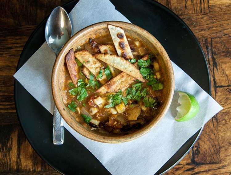 One Crazy House Instant Pot Dinners bowl of chicken tortilla soup on napkin with a spoon next to it