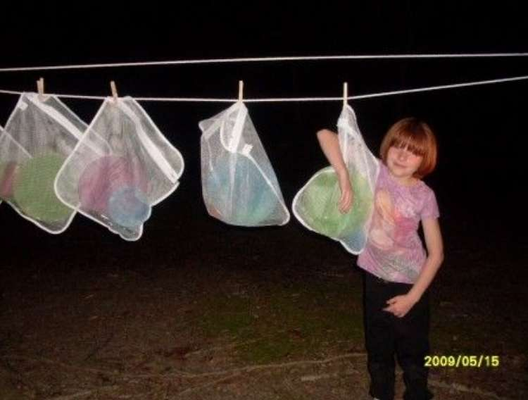 OneCrazyHouse Mesh Laundry Bags child standing in front of mesh bags hanging from a clothes line at night