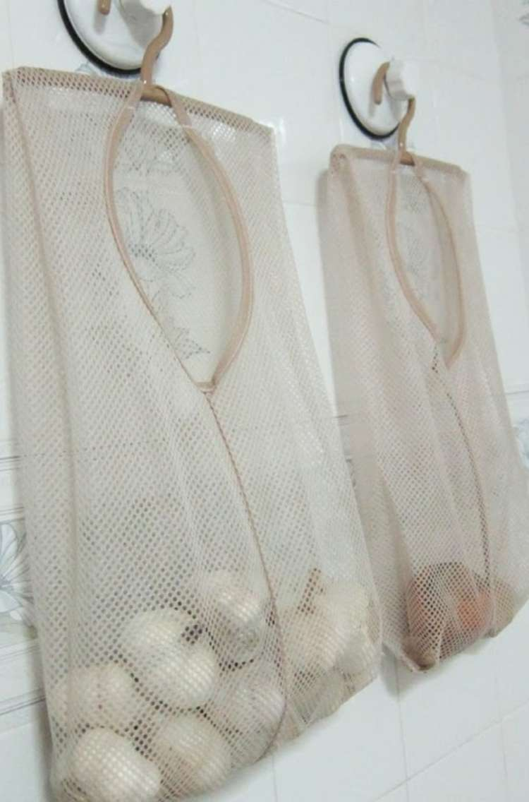 OneCrazyHouse Mesh Laundry Bags Mesh Bags hung from wall. One of the mesh bags has garlic, the other has potatos