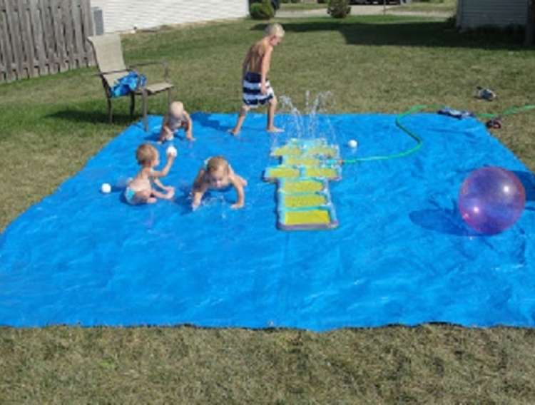 OneCrazyHouse Stay Cool without a pool 4 children playing on rubber mat on the ground with sprinkler spraying water in the middle