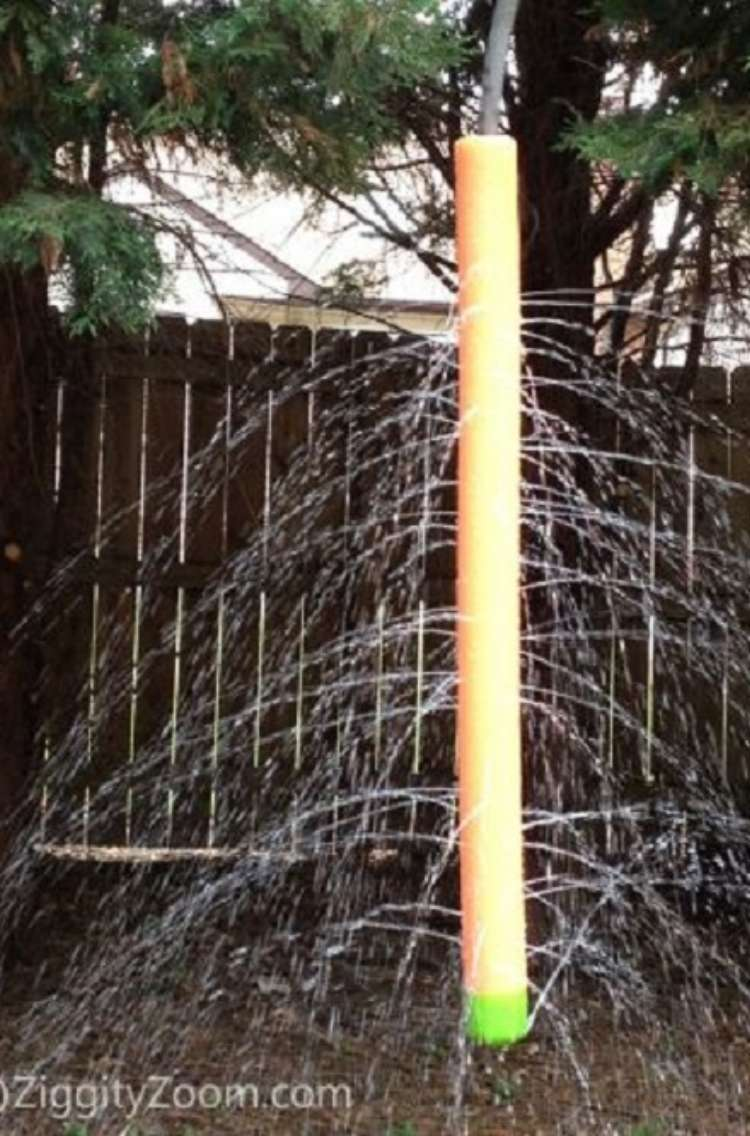 OneCrazyHouse Stay Cool without a pool pool noodle with holes hanging from tree with water pouring out of holes