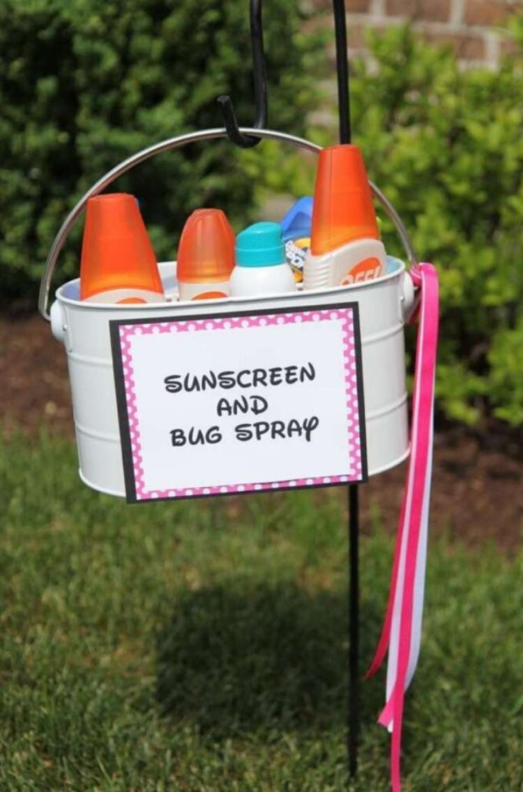 OneCrazyHouse pool storage basket filled with bug sprays and sunscreen hanging in a bukcet on a lawn