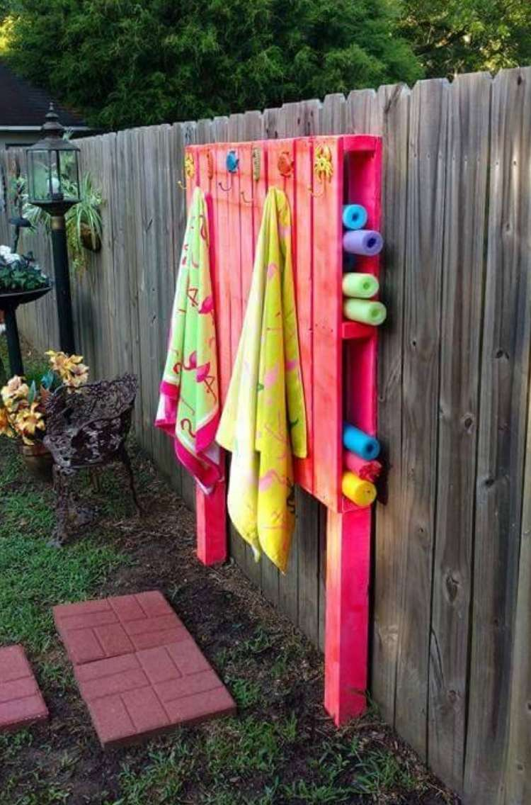 OneCrazyHouse pool storage pallet attached to a fence with towels hanging from hooks in front and pool noodles stored in holes on the side