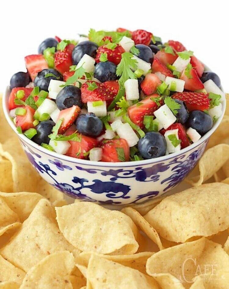 A fruit salad for the 4th of July that contains blueberries, strawberries, and jicama with cinnamon chips surrounding the bowl
