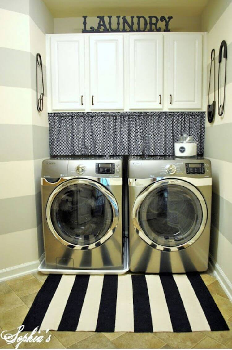 Laundry room with a valence and tension rod covering cords above a washer and dryer