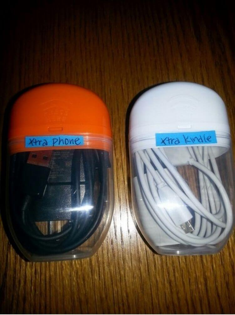 Empty Tic-Tac containers with cords stored inside and labeled with the type of cord it is holding