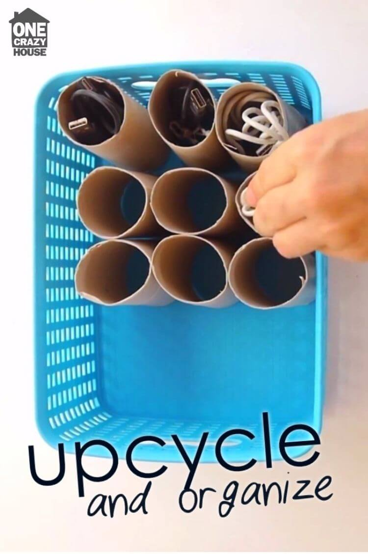 A basket containing empty toilet paper rolls filled with cords to organize different cables