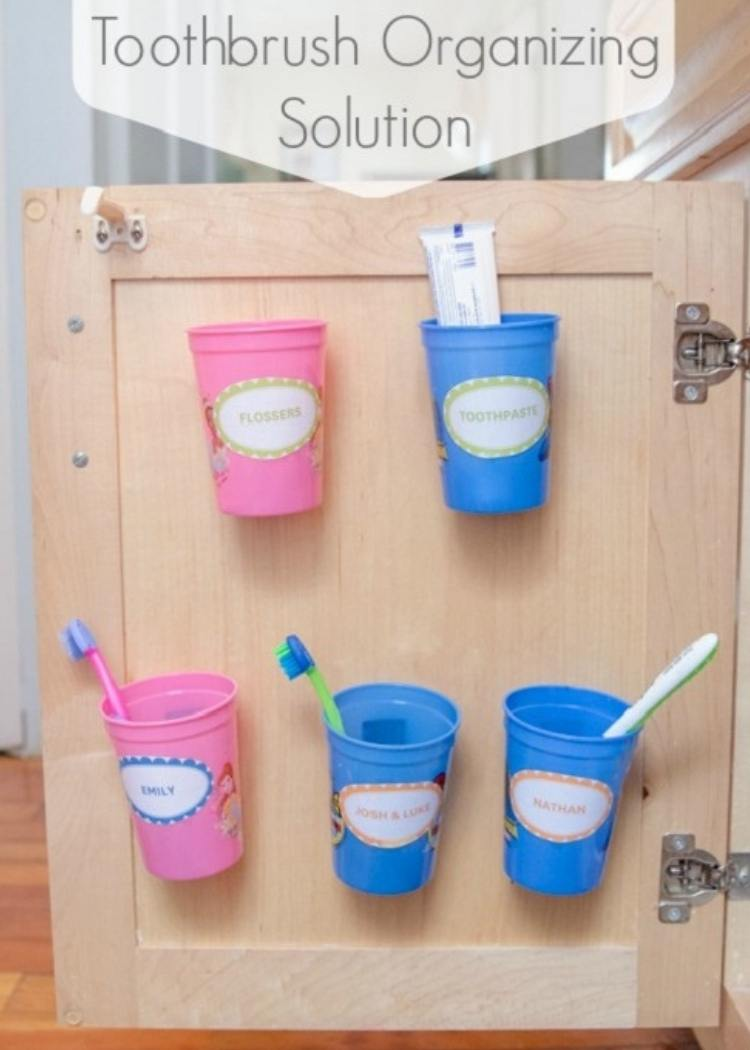 Pink & blue cups hang on inside of cabinet door to keep toothbrushes organized and clean. Fun idea for small kid's bathroom.
