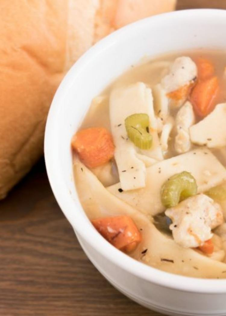 Chicken Noodle Soup - soup in white bowl with carrots, celery and flat short noodles. Bread love in background.