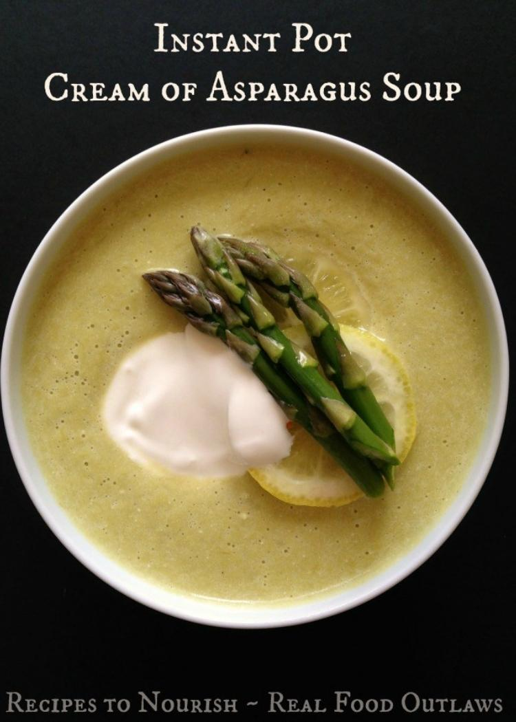 Cream of Asparagus Soup in white bowl, garnished with cooked asparagus, dollop of cream and slice of lemon, with black background.