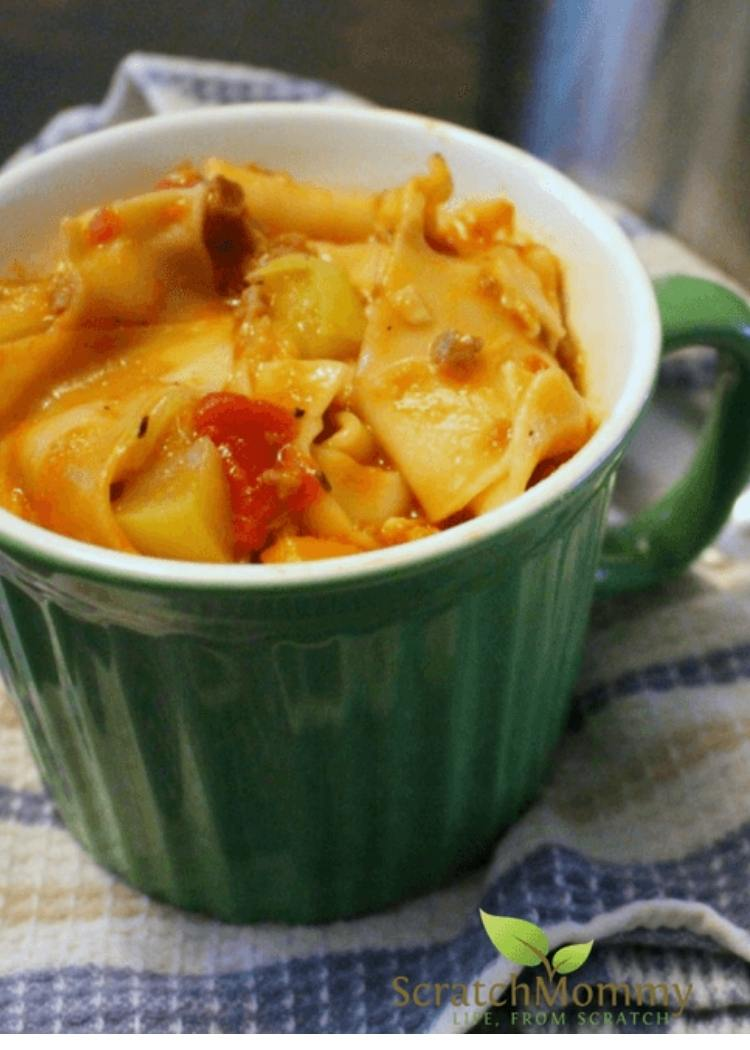 Lasagna Soup in a green soup mug. Soup contains lots of lasagna pieces in a tomato based soup.