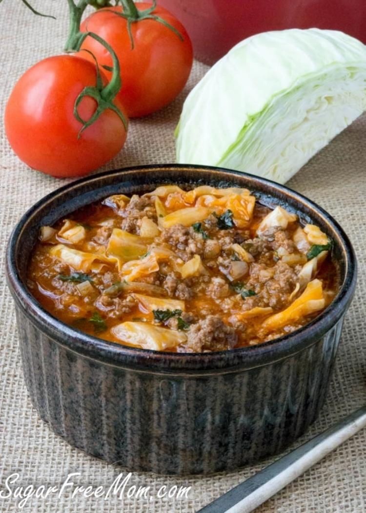 Low Calories Un-Stuffed Cabbage Roll Soup - A bowl of Un-Stuffed Cabbage Roll Soup in a small black casserole dish with fresh tomatoes and cabbage in the background.