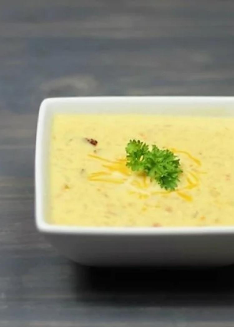 Low Carb Loaded Cauliflower Soup - a square bowl of cauliflower soup with bacon, cream cheese and cheddar cheese, garnished with parsley and shredded cheese.