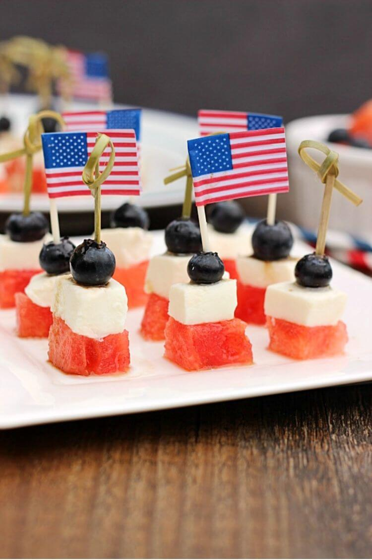 4th of July appetizer using skewers to hold together cut up watermelon, mozerella cheese, and blueberries