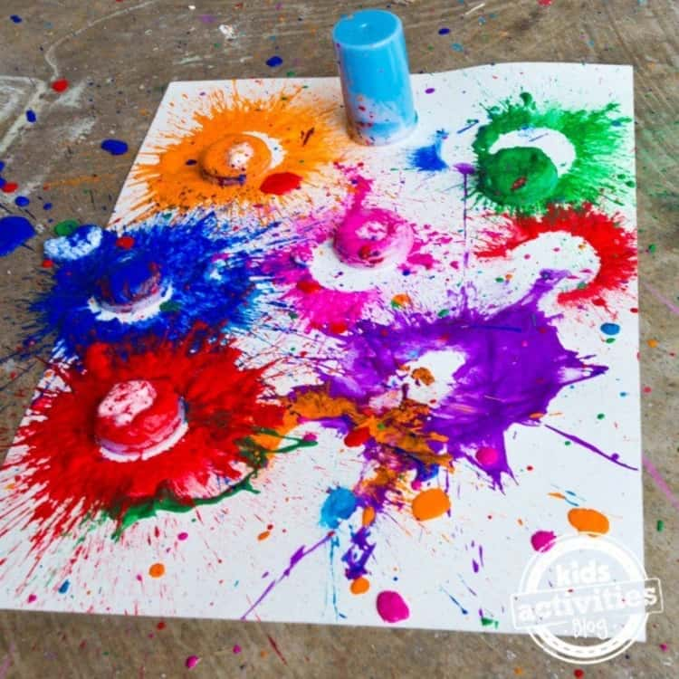 A photo of paint splashed onto a watercolor paper using paint bombs made from alka-seltzer tablets